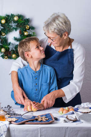 Happy senior mature woman, grandmother and young boy, grandson cooking, kneading dough, baking pie, cake,  cookies. Family time in the cozy kitchen. Seasonal winter Christmas activity at home. Standard-Bild