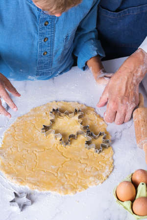Happy senior mature woman, grandmother and young boy, grandson cooking, kneading dough, baking pie, cake, cookies. Family time in the cozy kitchen. Seasonal winter Christmas activity at home.