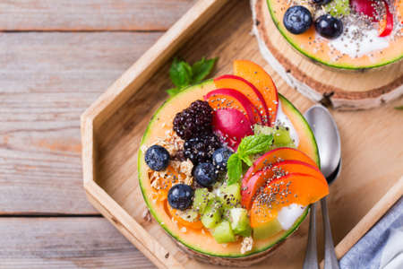 Healthy clean eating, dieting and nutrition, seasonal, summer breakfast concept. Fruit salad with yogurt in carved melon cantaloupe bowl on a kitchen table. Top view flat lay background Stock fotó