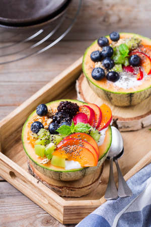 Healthy clean eating, dieting and nutrition, seasonal, summer breakfast concept. Fruit salad with yogurt in carved melon cantaloupe bowl on a kitchen table. Stock fotó
