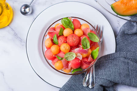 Healthy clean eating, dieting and nutrition, seasonal, summer meal lunch concept. Fruit salad with melon cantaloupe, watermelon and prosciutto in a bowl on kitchen table. Top view flat lay background