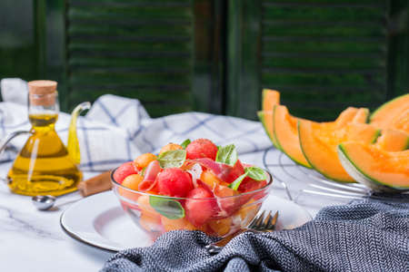 Healthy clean eating, dieting and nutrition, seasonal, summer meal lunch concept. Fruit salad with melon cantaloupe, watermelon and prosciutto in a bowl on a kitchen table.