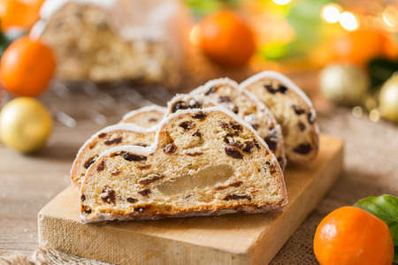 Seasonal food and drink, winter concept. Traditional European German homemade Christmas cake, pastry dessert Stollen on a wooden backgrounds with festive decoration.