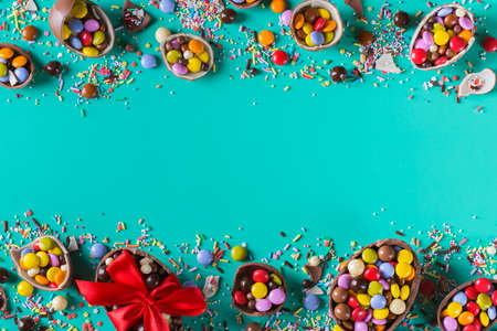 Easter frame with chocolate eggs and sweets on a turquoise, green, blue background. Copy space, top view, flat lay