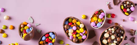 Easter frame with chocolate eggs and sweets on a pink background. Banner, top view, flat lay
