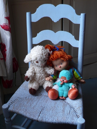 Doll, stuffed lamb and blue monkey, sitting on a chair