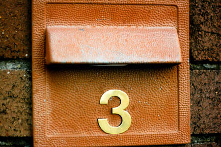 numerical: Number 3 in gold on a letter box