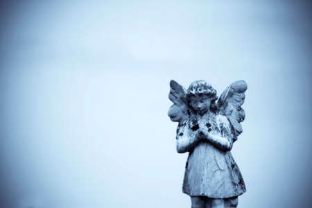 gravesite: A stone angel with a blue background
