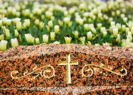 grave stones: A Cross on headstone with yellow flowers