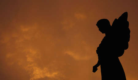 angel headstone: Silhouette of a Statue of an Angel with Storm Clouds