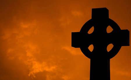 A Silhouette of a Cross with Clouds at Sunset photo