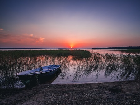 Sunset on the lake, fishing boat on the shore, Russia