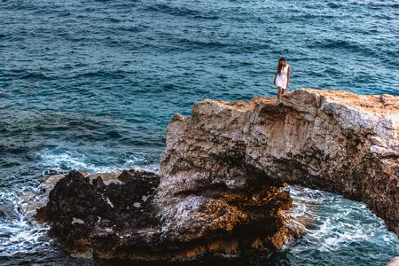 Woman in white dress on the beautiful natural rock arch near of Ayia Napa, Cavo Greco and Protaras on Cyprus island, Mediterranean Sea. Legendary bridge lovers. Banco de Imagens