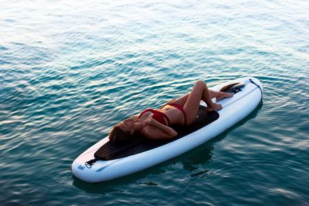 Junge schöne Frau, die im Meer auf einem SUP-Brett entspannt. Das Mädchen nimmt im Urlaub am Strand der Insel ein Sonnenbad. Standard-Bild