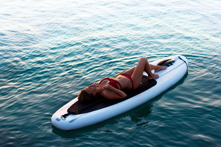 Young beautiful woman relaxing in the sea on a SUP board. The girl sunbathes on the beach of the island on vacation. Archivio Fotografico