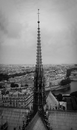 The spire of Notre Dame de Paris, panoramic view of Paris and river Seine from the roof of Notre Dame cathedral, France. Cloudy weather.