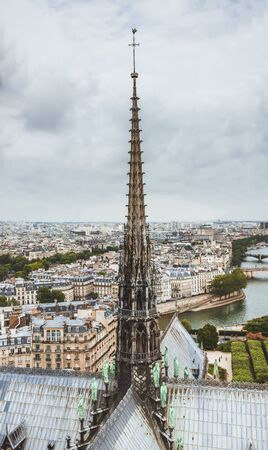 The spire of Notre Dame de Paris, panoramic view of Paris and river Seine from the roof of Notre Dame cathedral, France. Cloudy weather. Stock Photo
