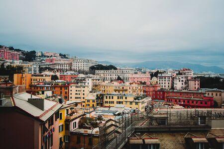 Viele schöne alte italienische Häuser gemalt in hellen Farbenbergen im Hintergrund. Ein erstaunliches Stadtbild einiger Sozialwohnungen in Genua, das in den 60er Jahren über den Hügeln der Stadt an bewölktem Tag gebaut wurde,