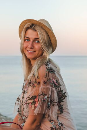 Young pretty woman with blond hair in pink shirt and hat sitting on the stones near the sea at sunrise