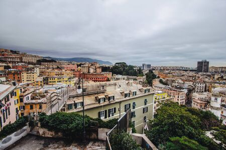 Many beautiful old italian houses painted in bright colors with mountains on the background.An amazing cityscape of some public housing in Genova built in the 60s over hills of the city in cloudy day,
