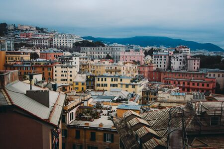 Many beautiful old italian houses painted in bright colors with mountains on the background.An amazing cityscape of some public housing in Genova built in the 60s over hills of the city in cloudy day, 스톡 콘텐츠 - 131953308