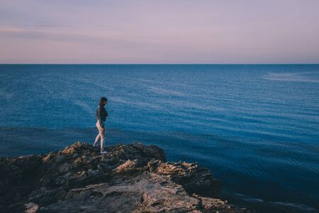 Woman traveler standing near sea on top of cliff in summer mountains and enjoying view of sea and nature. Cape Greco, Cyprus, Mediterranean Sea. Sunrise Stock Photo
