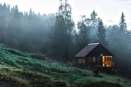 Small old wooden house in foggy forest. Mountains scenery. Nature conceptual image