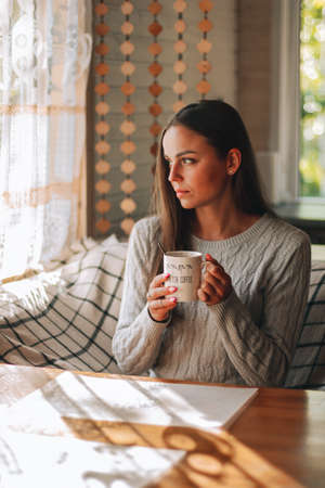Beautiful young woman resting at home with a cup of coffee in stylish interior near window. Coffee break Stock fotó