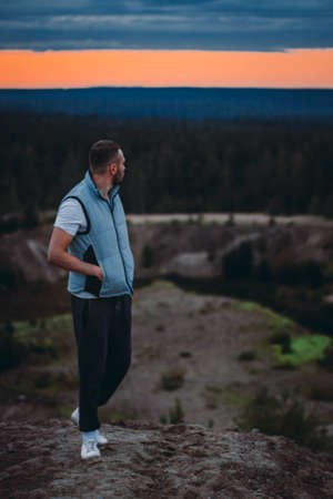 Attractive young man standing on hill and looking at the scenic view of the forest and sunset cloudy sky 版權商用圖片