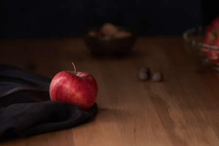 A bright red apple on a dark brown fabric with nuts in the background and a moody lighting
