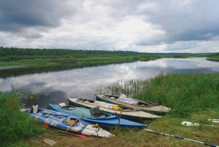 Canoes rest on shore of a river in summer                               Stock Photo