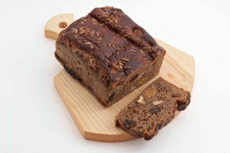 Loaf of brown bread with ingredients: prunes, dried apricots, nuts,  sunflower seeds, and slice on wood cutting board                                Stock Photo