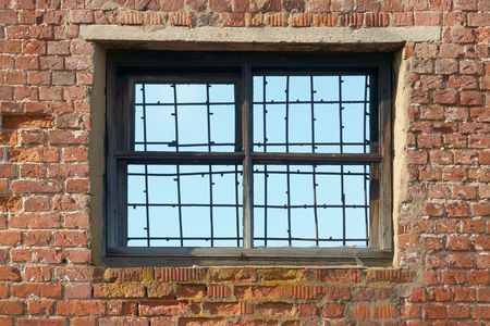 Antique brick wall with broken grated window                                photo