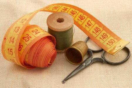 Сollection of sewing ancient tools and supplies in a sewing kit on canvas                                 photo