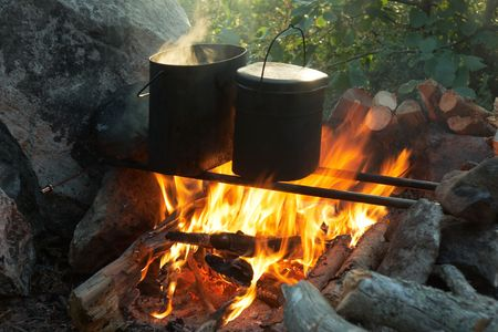 Kettles over campfire around rock and firewood photo