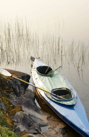 Canoe with oar and fishing-tackle on shore of lake in summer  Stock Photo