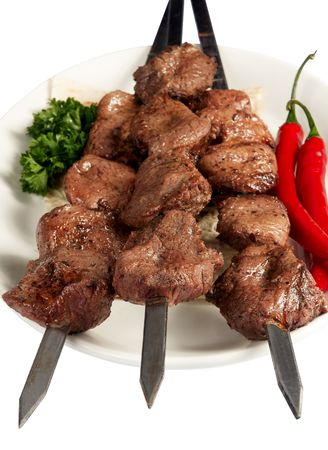 meat skewers: Grilled meat on skewer with parsley, paprika and cake on white plate Stock Photo