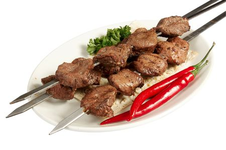 Grilled meat on skewer with parsley, paprika and cake on white plate photo