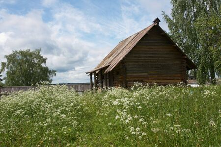 Old wooden barn and summer meadow