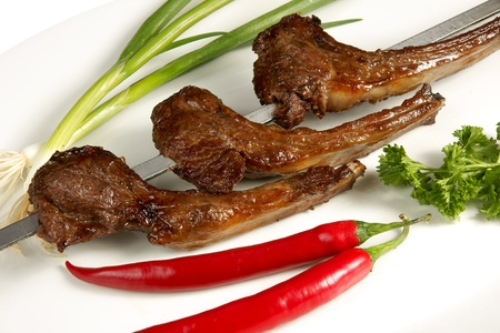 Shish kebab with parsley, paprika and onion on white plate    photo