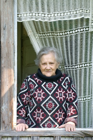 Elderly smile woman is looking out open window of old summer cottage (Russia)         Stock Photo