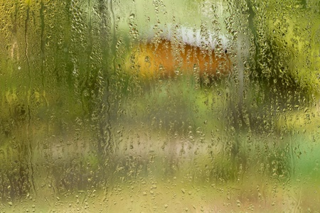 drizzle: Raindrops on window with house  and trees as background   Stock Photo