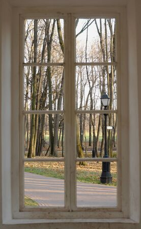 view window: Autumn park with street lamp and path from wooden window Stock Photo