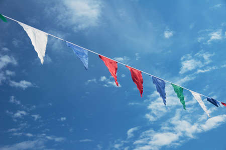 Colored flags on blue sky  background Stock Photo