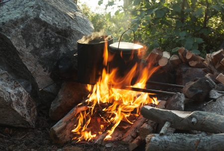 Kettles over campfire  around rock with firewood