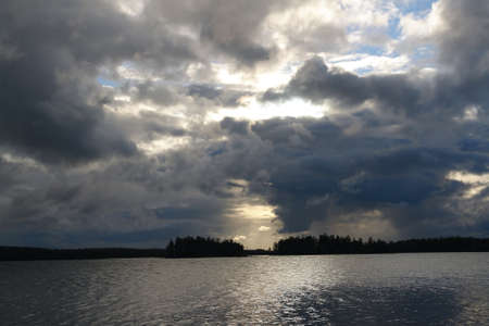 approaching: Lake under dark cloudy sky before approaching storm Stock Photo