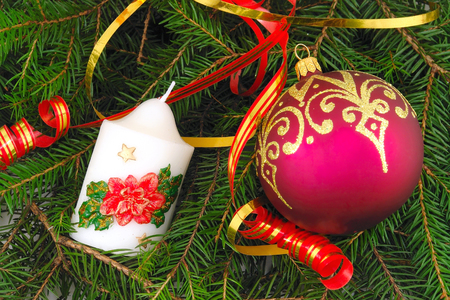 Christmas ball and candle with ribbon on spruce  branch                               Stock Photo