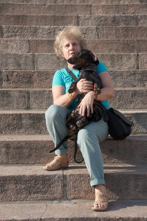 Middleaged woman holding dachshund on stairs