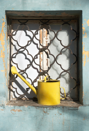 Yellow iron watering can in window with iron grating of old house