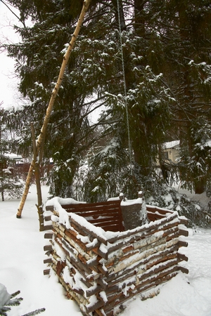 Wooden ancient water well in country in winter Stock Photo